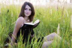 La muchacha que se sienta en una hierba, leyendo un libro Fotografía de archivo libre de regalías