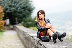 La muchacha que se sienta en una pared mira Imagen de archivo