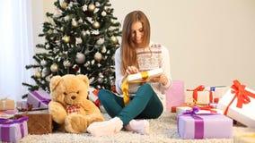 La muchacha que se sienta por el árbol de navidad y los regalos se abre almacen de metraje de vídeo