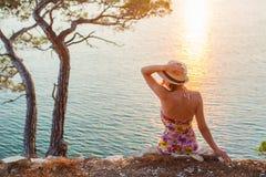 La muchacha que se sienta por el mar en la puesta del sol y el sombrero lleva a cabo las manos Fotografía de archivo libre de regalías