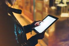 La muchacha que se sostiene en manos en la tableta limpia en blanco de la pantalla en bokeh del resplandor del fondo se enciende  foto de archivo libre de regalías