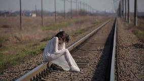La muchacha que sorprende en el vestido translúcido blanco soplado por el viento y con maquillaje de la cera en cara en forma de metrajes
