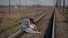 La muchacha que sorprende en el vestido translúcido blanco soplado por el viento y con maquillaje de la cera en cara en forma de almacen de metraje de vídeo