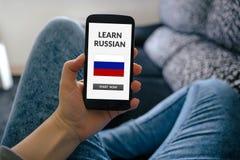La muchacha que sostiene el teléfono elegante con aprende el concepto ruso en la pantalla fotografía de archivo