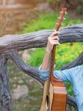 La muchacha que sostiene la guitarra se enfría hacia fuera en el jardín Fotografía de archivo libre de regalías