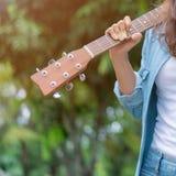 La muchacha que sostiene la guitarra se enfría hacia fuera en el jardín Foto de archivo libre de regalías