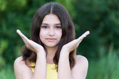 La muchacha que sostiene las palmas de las manos sube afuera Imagen de archivo libre de regalías