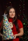 La muchacha que sostiene un árbol de navidad en el fondo del centelleo se enciende Fotografía de archivo libre de regalías