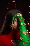 La muchacha que sostiene un árbol de navidad en el fondo del centelleo se enciende Fotografía de archivo