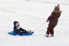 La muchacha que tira de niños del muchacho embroma nieve del trineo del trineo largo  Imagenes de archivo