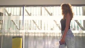 La muchacha que va al airplaine, entra en el terminal en el aeropuerto, celebrando el pasaporte y el boleto almacen de metraje de vídeo