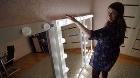 La muchacha que va a apagar la luz de los espejos del maquillaje Fabricación de espejos del maquillaje almacen de video