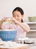 La muchacha quiebra los huevos en el tazón de fuente para el proyecto de la hornada Imagen de archivo libre de regalías