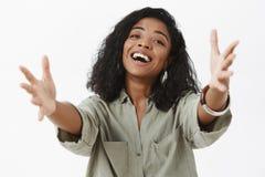 La muchacha quiere abrazos Retrato de la mujer afroamericana femenina encantadora amistosa en la blusa que tira de las manos haci fotos de archivo libres de regalías