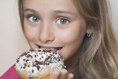 La muchacha quiere comer los anillos de espuma Una muchacha mira con un apetito los anillos de espuma coloridos fotos de archivo