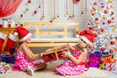 La muchacha quiere pero no puede coger un regalo de la Navidad de las otras muchachas Fotos de archivo