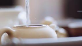 La muchacha quita suavemente la tapa de la caldera y llena el agua hirvienda en las hojas de té Primer, ceremonia de té metrajes