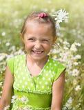 La muchacha ríe entre las flores de la margarita Muchacha sonriente en un campo de la tarima Fotografía de archivo