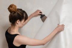 La muchacha rasga apagado el papel pintado viejo del muro de cemento y sostiene una espátula imágenes de archivo libres de regalías