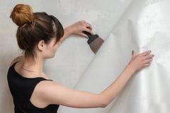 La muchacha rasga apagado el papel pintado viejo del muro de cemento y sostiene una espátula imagen de archivo libre de regalías