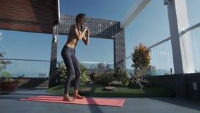 La muchacha realiza ejercicio en terraza del tejado debajo del cielo