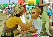 La muchacha realiza el maquillaje creativo para el muchacho Fotos de archivo libres de regalías