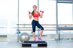 La muchacha realiza el paso cardiio con pesas de gimnasia en un gimnasio Imagenes de archivo