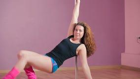 La muchacha realiza el truco acrobático cerca del polo metrajes