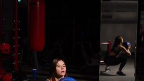 La muchacha realiza posiciones en cuclillas con lanzar la bola en sus manos Entrenamiento aerobio almacen de video