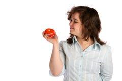 La muchacha rechoncha en la camisa blanca demuestra el tomate. Fotos de archivo