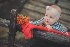 La muchacha recién nacida del bebé con los ojos azules que llevan el tartán comprueba la camisa de vestir y el pañuelo rosado del Imagen de archivo libre de regalías