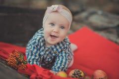 La muchacha recién nacida del bebé con los ojos azules que llevan el tartán comprueba la camisa de vestir y el pañuelo rosado del Fotos de archivo