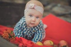 La muchacha recién nacida del bebé con los ojos azules que llevan el tartán comprueba la camisa de vestir y el pañuelo rosado del Imagen de archivo