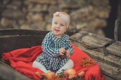 La muchacha recién nacida del bebé con los ojos azules que llevan el tartán comprueba la camisa de vestir y el pañuelo rosado del Foto de archivo