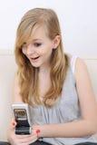 La muchacha recibe los sms y las sonrisas sorprendidos Fotografía de archivo libre de regalías