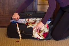 La muchacha recoge cosas en una maleta Foto de archivo libre de regalías