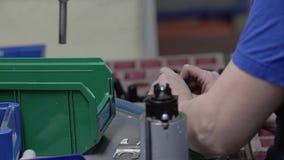 La muchacha recoge el dispositivo en una empresa industrial Primer de sus manos metrajes