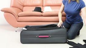 La muchacha recoge la ropa en una maleta almacen de video