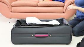 La muchacha recoge la ropa en una maleta metrajes