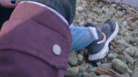 La muchacha recoge las hojas en la orilla del río almacen de video