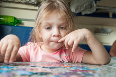 La muchacha recoge rompecabezas mientras que en un tren Imagen de archivo