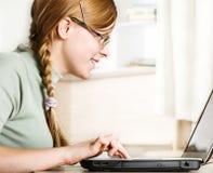 La muchacha Redheaded utiliza el ordenador personal Fotografía de archivo libre de regalías