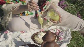 La muchacha regordeta pone una cuchara de la miel en las crepes con el requesón que se sienta en la hierba en el campo Hecho en c almacen de video