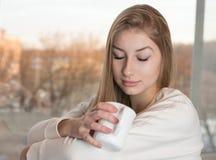 La muchacha relajada está disfrutando del aroma de una taza Foto de archivo