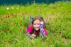 La muchacha relajada feliz del niño en una primavera florece el prado foto de archivo libre de regalías