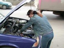 La muchacha repara el coche Fotos de archivo libres de regalías