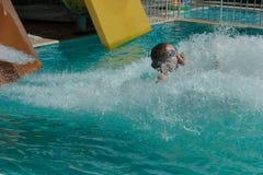 La muchacha resbala abajo de la diapositiva dentro de la piscina Fotografía de archivo