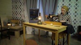 La muchacha retra de la costurera cose el paño con la máquina de coser de la vieja mano manual Mujer que trabaja en casa o taller metrajes