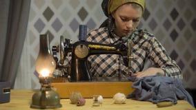 La muchacha retra de la costurera cose el paño con la máquina de coser de la vieja mano manual La mujer trabaja en casa o taller  almacen de video