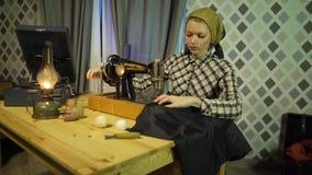 La muchacha retra hermosa de la costurera cose el paño con la máquina de coser de la vieja mano manual Mujer que trabaja en casa  metrajes